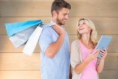 Zusammengesetztes Bild von den attraktiven jungen Paaren, welche die Einkaufstaschen betrachten Tabletten-PC halten Lizenzfreie Stockbilder
