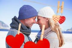 Zusammengesetztes Bild von den attraktiven Paaren, die an einander auf dem Strand in der warmen Kleidung lächeln Stockbilder