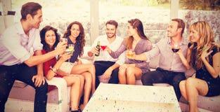 Zusammengesetztes Bild von den Freunden, die Getränke sprechen und haben Lizenzfreie Stockbilder