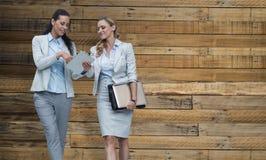 Zusammengesetztes Bild von den Geschäftsfrauen, die digitale Tablette verwenden Stockbild