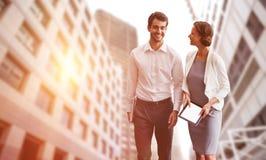 Zusammengesetztes Bild von den Geschäftskollegen, die digitale Tablette beim Gehen verwenden Lizenzfreie Stockfotografie