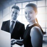 Zusammengesetztes Bild von den Geschäftsleuten, die mit einem Laptop stehen Stockbilder
