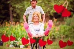 Zusammengesetztes Bild von den glücklichen älteren Paaren, die mit einer Schubkarre spielen Stockbilder