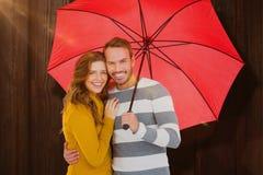 Zusammengesetztes Bild von den glücklichen jungen Paaren, die roten Regenschirm halten Lizenzfreies Stockbild