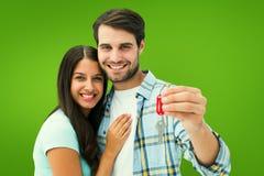 Zusammengesetztes Bild von den glücklichen jungen Paaren, die Schlüssel des neuen Hauses halten Stockbild
