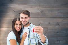 Zusammengesetztes Bild von den glücklichen jungen Paaren, die Schlüssel des neuen Hauses halten Lizenzfreie Stockfotos