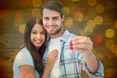 Zusammengesetztes Bild von den glücklichen jungen Paaren, die Schlüssel des neuen Hauses halten Lizenzfreies Stockfoto