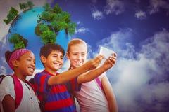 Zusammengesetztes Bild von den glücklichen Kindern, die selfie im Schulkorridor nehmen Lizenzfreie Stockfotografie