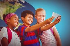 Zusammengesetztes Bild von den glücklichen Kindern, die selfie im Schulkorridor nehmen Stockbilder