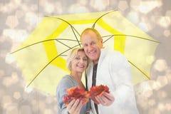 Zusammengesetztes Bild von den glücklichen reifen Paaren, die Herbstlaub unter Regenschirm zeigen stockfotografie
