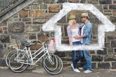 Zusammengesetztes Bild von den jungen Paaren der Hüfte, die durch Backsteinmauer mit ihren Fahrrädern umarmen Lizenzfreie Stockfotografie