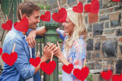 Zusammengesetztes Bild von den jungen Paaren der Hüfte, die an einander durch Geländer lächeln Lizenzfreies Stockfoto