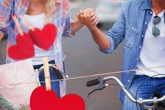 Zusammengesetztes Bild von den jungen Paaren der Hüfte, die für ein Fahrrad gehen, reiten Stockfotos