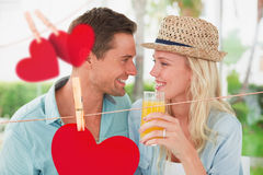 Zusammengesetztes Bild von den jungen Paaren der Hüfte, die zusammen Orangensaft trinken Lizenzfreies Stockfoto