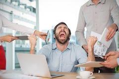 Zusammengesetztes Bild von den Kollegen, die frustrierten Geschäftsmann am Schreibtisch bereitstehen stockbild