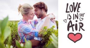 Zusammengesetztes Bild von den lächelnden Paaren, die Außenseite unter den Büschen umfassen Lizenzfreies Stockfoto