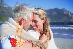 Zusammengesetztes Bild von den lächelnden Paaren, die auf dem Strand unter Decke sitzen Stockfoto