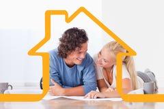 Zusammengesetztes Bild von den lächelnden Paaren, die in ein neues Haus sich bewegen Stockfoto