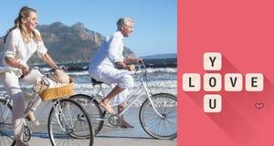 Zusammengesetztes Bild von den lächelnden Paaren, die ihre Fahrräder auf den Strand reiten Stockfotos