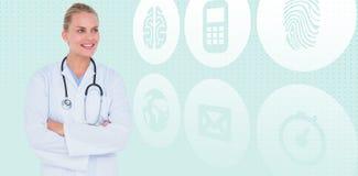 Zusammengesetztes Bild von den lächelnden stehenden Armen der Ärztin gekreuzt Stockbild