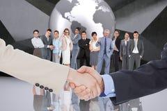 Zusammengesetztes Bild von den lächelnden Geschäftsleuten, die Hände beim Betrachten der Kamera rütteln Lizenzfreies Stockbild