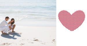 Zusammengesetztes Bild von den netten Paaren, die ein Herz im Sand zeichnen Lizenzfreie Stockfotos