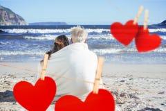 Zusammengesetztes Bild von den Paaren, die auf dem Strand unter der Decke heraus schaut zum Meer sitzen Lizenzfreie Stockbilder