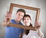 Zusammengesetztes Bild von den Paaren, die Rahmen vor ihnen halten Lizenzfreie Stockfotografie