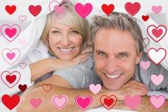 Zusammengesetztes Bild von den Paaren, die unter den Abdeckungen lächeln Lizenzfreie Stockfotografie