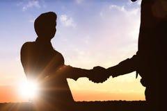 Zusammengesetztes Bild von den Schattenbildern, die Hände rütteln Lizenzfreies Stockbild