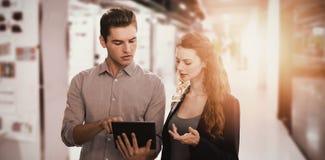 Zusammengesetztes Bild von den starken Geschäftsleuten, die eine digitale Tablette verwenden stockfoto