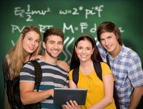 Zusammengesetztes Bild von den Studenten, die digitale Tablette am Collegekorridor verwenden lizenzfreie stockfotos