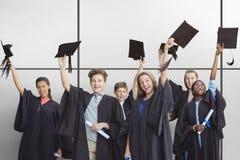 Zusammengesetztes Bild von den Studenten, die Doktorhuten halten stockbilder