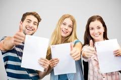 Zusammengesetztes Bild von den Studenten, die Prüfung halten und oben Daumen tun Stockfotos
