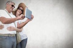 Zusammengesetztes Bild von den Urlaub machenden Paaren, die Foto machen Stockbild