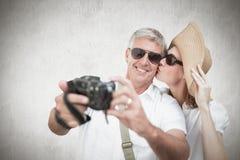 Zusammengesetztes Bild von den Urlaub machenden Paaren, die Foto machen Lizenzfreie Stockfotos