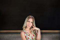 Zusammengesetztes Bild von die Stirn runzeln recht blonde tragende Aufstellung des geblümten Kleids Lizenzfreie Stockbilder