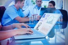 Zusammengesetztes Bild von Doktor schreibend auf Tastatur mit ihrem Team hinten Stockbilder