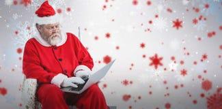 Zusammengesetztes Bild von ernstem Weihnachtsmann, der Laptop verwendet Stockbilder