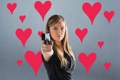 Zusammengesetztes Bild von femme fatale Gewehr auf Kamera zeigend Stockbild
