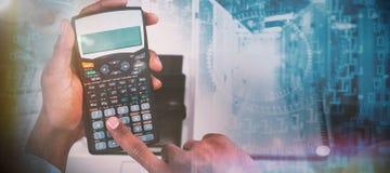 Zusammengesetztes Bild von geernteten Händen des Geschäftsmannes unter Verwendung des Taschenrechners lizenzfreies stockfoto