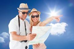 Zusammengesetztes Bild von glücklichen touristischen Paaren unter Verwendung der Karte und des Zeigens Lizenzfreie Stockfotos