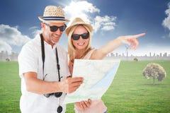 Zusammengesetztes Bild von glücklichen touristischen Paaren unter Verwendung der Karte und des Zeigens Lizenzfreie Stockfotografie
