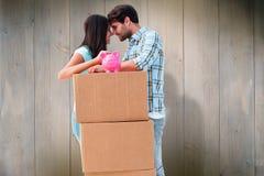 Zusammengesetztes Bild von glücklichen jungen Paaren mit beweglichen Kästen und Sparschwein Lizenzfreie Stockfotos