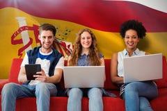 Zusammengesetztes Bild von jungen Erwachsenen unter Verwendung der elektronischen Geräte auf Couch Stockfotografie