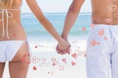 Zusammengesetztes Bild von jungen Paaren im Badebekleidungshändchenhalten Stockfoto