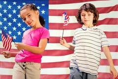 Zusammengesetztes Bild von Kindern mit amerikanischen Flaggen stockfotos