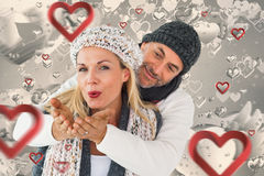 Zusammengesetztes Bild von lächelnden Paaren im Winter arbeiten die Aufstellung um Stockfoto