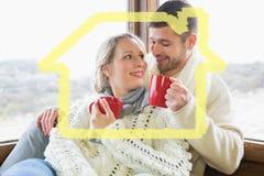 Zusammengesetztes Bild von liebevollen Paaren im Winter tragen trinkenden Kaffee gegen Fenster Stockfotos