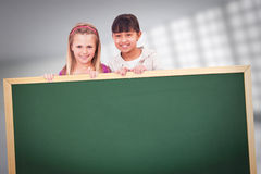 Zusammengesetztes Bild von Mädchen hinter einer Leerplatte Lizenzfreie Stockfotos